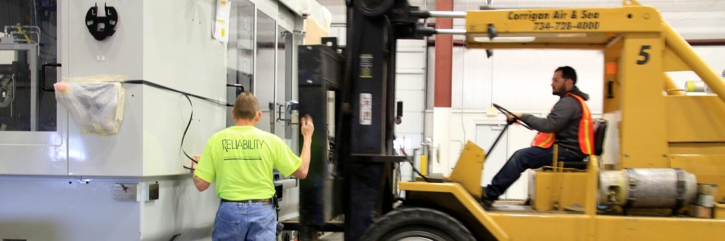 person drives extremely large forklift while another person spots for safety