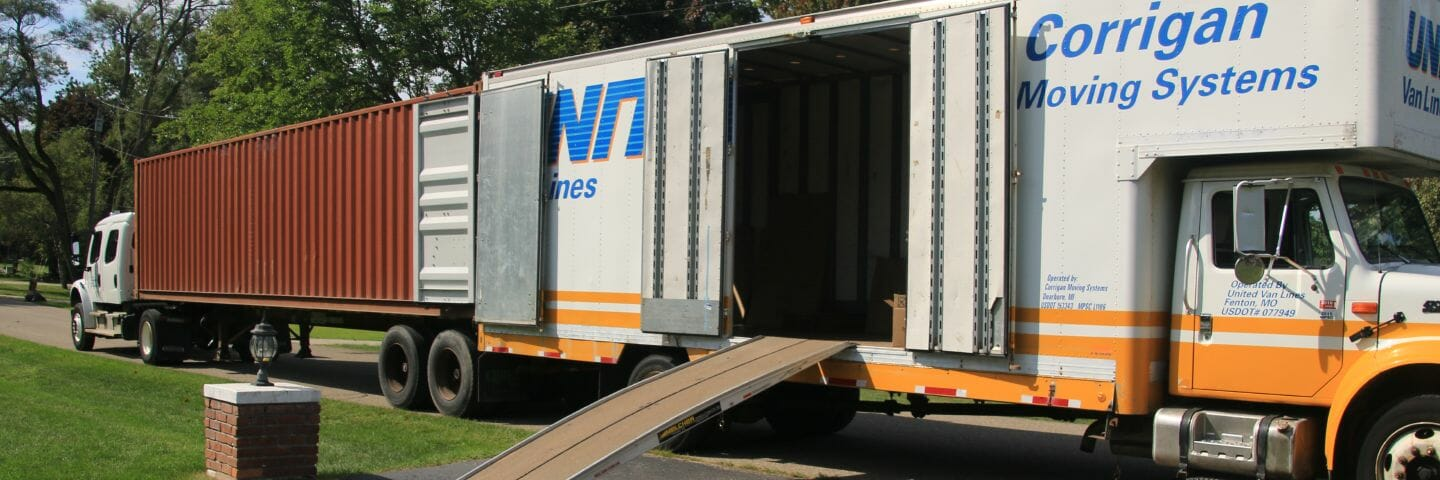 international shipping container parked back to back with moving truck