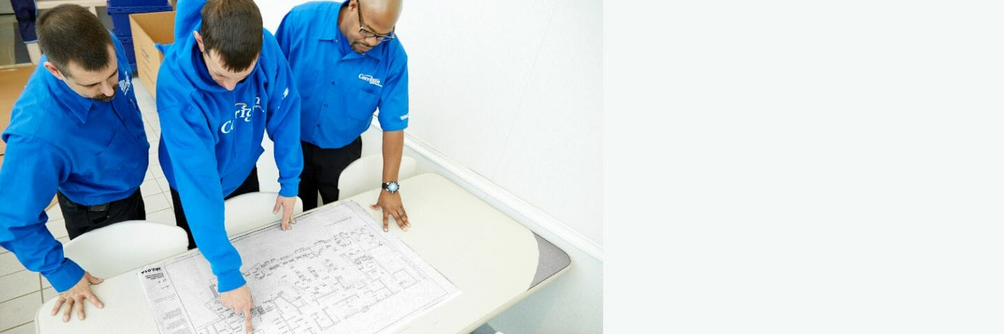 three men in blue examining and pointing at blueprints