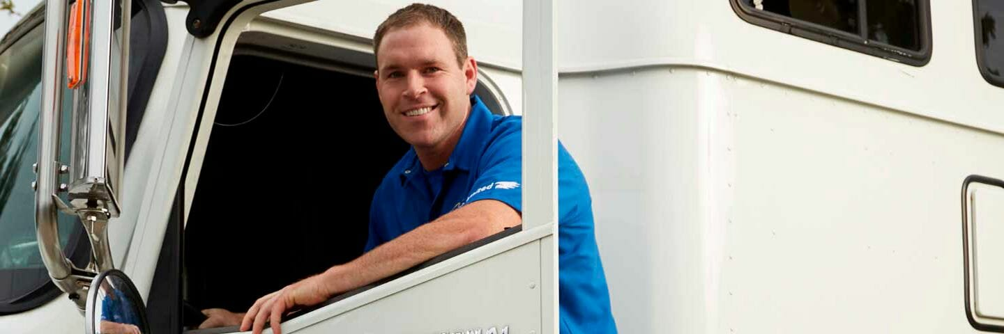 moving company truck driver climbing into cab of tractor trailer