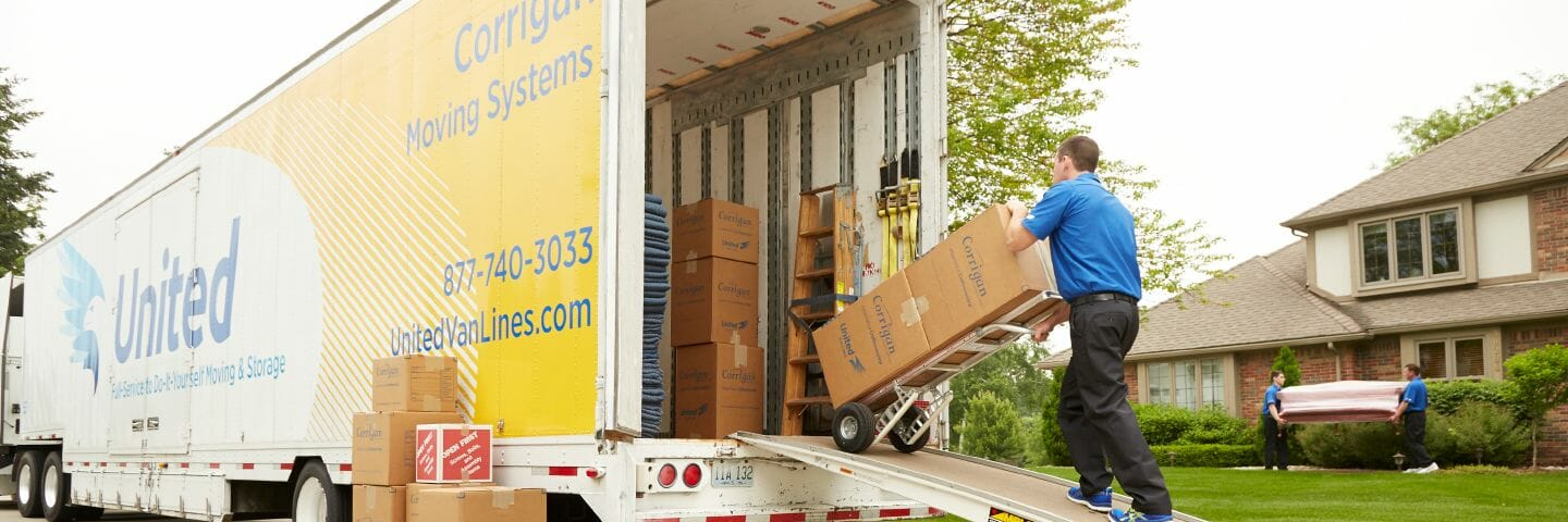 mover pushing dolly of boxes into moving tractor trailer