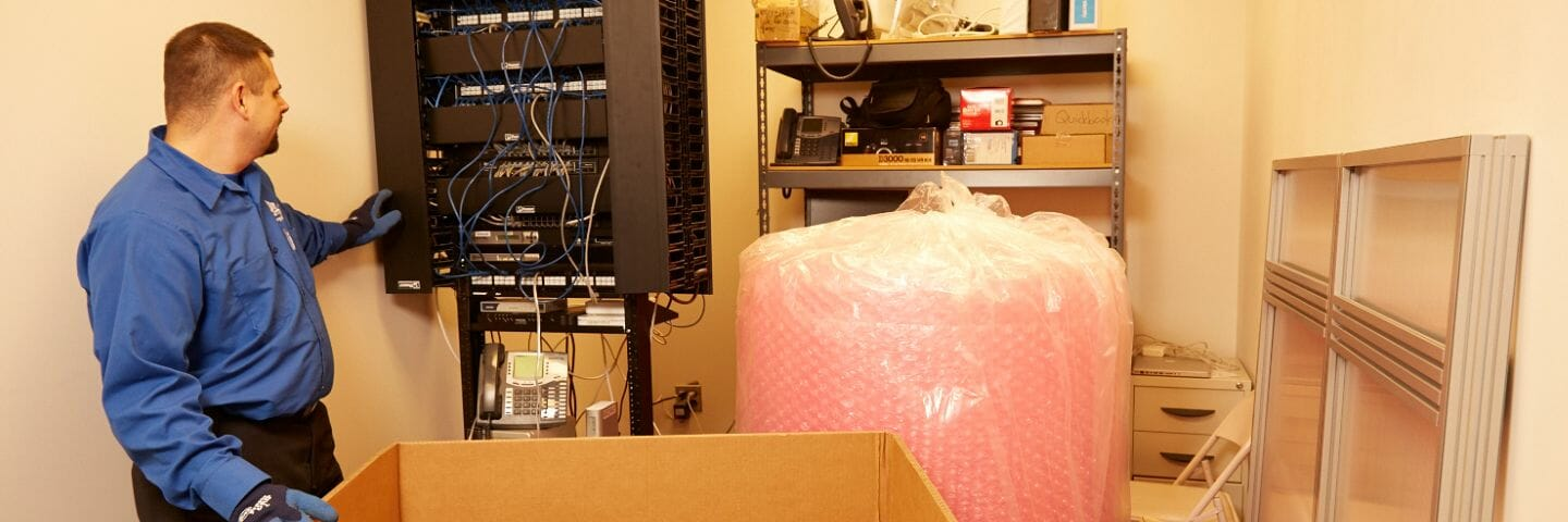 mover inspecting server with bubble wrap nearby